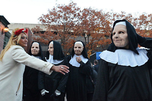 Salem: A woman with demon horns approaches a group dressed as a nuns for a picture. photo by Mark Teiwes / Salem News