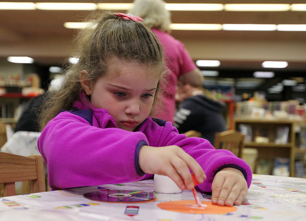 Danvers: Lucy Osborne, 3 1/2, of Danvers concentrates while gluing together a pumpkin CD on Thursday evening at the Peabody Institute Library in Danvers. David Le/Salem News