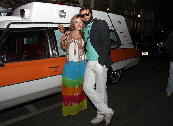 Isa Meses, left, and Agustin Rivero, of Roslindale, hang around next to an old ambulance in downtown Salem on Halloween night. David Le/Staff Photo.