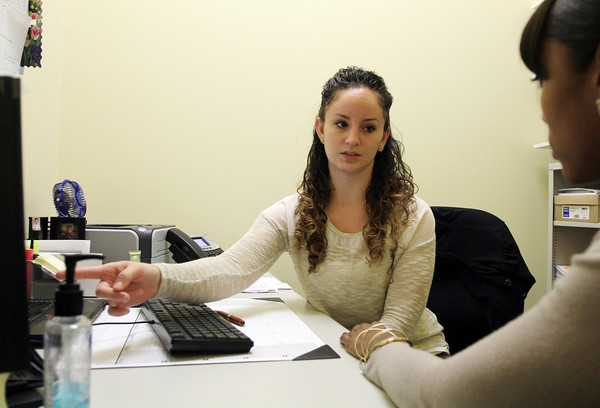 Salem: Sabrina Correa, a certified application councilor at the Salem Family Health Center, works with a resident to re-register for health insurance coverage under Obamacare which can be completed online. David Le/Salem News