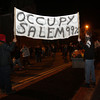 "A few people hold up an ""Occupy Salem 99%"" sign. David Le/Staff Photo."