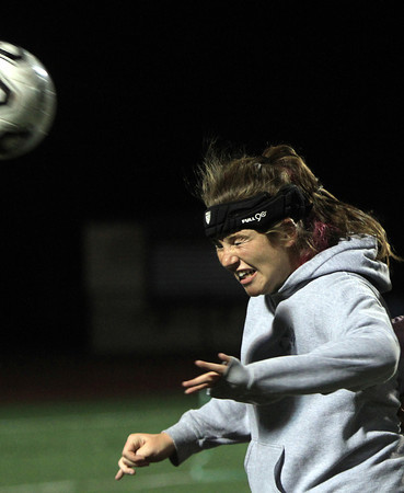 Peabody: Bishop Fenwick junior Emma Harrington goes through a head ball drill at practice on Tuesday evening. Several Crusaders players wear special headbands that help prevent concussions. David Le/Salem News