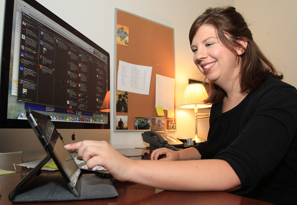 Salem: Amanda Voodre, web manager at Salem State University, is in charge of all the social media outlets for the university. Voodre keeps tabs on everything going on around campus using Facebook and Twitter which she has queued up on her iMac desktop as well as her iPad and iPhone. David Le/Salem News