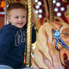 Salem: Three-year-old Noah Thompson, of Salem, smiles while riding the horse carousel at the Salem Haunted Happenings Carnival on Derby St. on Friday evening. David Le/Salem News