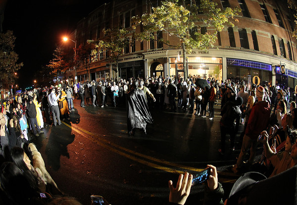 Salem: A large crowd of people gather in a circle as Bane and Batman have a staged fight in the middle of Washington St. on Thursday evening. David Le/Salem News