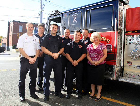 Danvers: From left, Captain Ken Reardon, Paul Lapointe, Steve Deroche, Pete Carter, Brandon Lamson, Jim Ciman, and Nancy Libby, of the Danvers Fire Department stand in front of one of their engines displaying a pink ribbon for breast cancer awareness. The firefighters also will wear pink ribbons on their uniforms throughout the month of October. David Le/Salem News