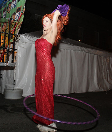 Lindsey Hollett, of Salem dances with a hula-hoop near the music stage on Washington St. on Halloween night. David Le/Staff Photo.