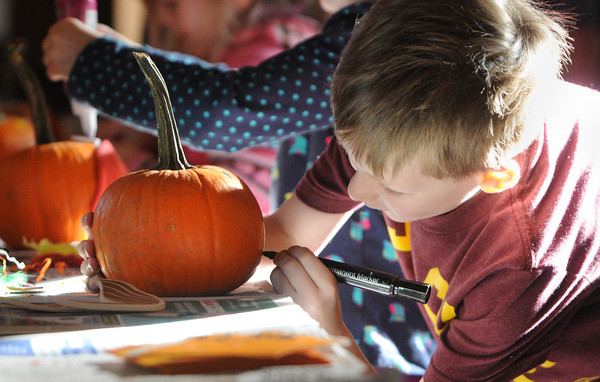 Marblehead:<br /> Billy Sidwell, 7, of Marblehead, decorates his pumpkin at the pumpkin decorating workshop at Marblehead Museum.<br /> Photo by Ken Yuszkus / The Salem News, Wednesday, October 30, 2013.