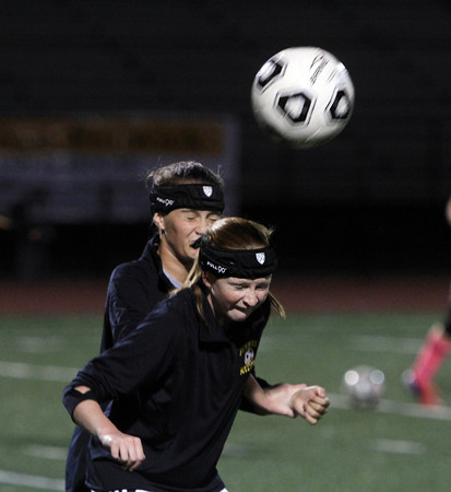 Peabody: Bishop Fenwick freshmen Emily Smith, right, and Emily Charette, battle for a header during practice on Tuesday evening. Some Crusaders players sport special headbands to help prevent concussions. David Le/Salem News