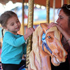 Salem: Rylie Batchelder, 3, smiles as she takes a ride on a horse carousel at the Salem Haunted Happenings Carnival with her aunt Lauren Famico, of Salem, on a warm Friday afternoon. David Le/Salem News