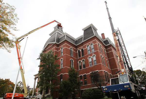 Peabody: A large crane hoists an iron fence up to the top of Peabody City Hall where they are getting placed on the roof. David Le/Salem News