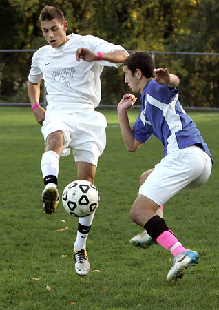 Danvers:<br /> St. John's Prep's Michael Lanza, left, kicks the ball as Danvers' Kyle Cahill  tries to get a hold of the ball at the Danvers at St. John's Prep boys soccer game.<br /> Photo by Ken Yuszkus, The Salem News,  Monday, October 14, 2013.