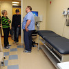 "Danvers:<br /> From left, Diane and Gordon Wood of Danvers talk with medical assistant Dan Ducheneau while on tour of one of the exam rooms at the open house for new ""Urgent Care"" facility at Mass General/North Shore Center for Outpatient Care<br /> Photo by Ken Yuszkus, The Salem News, Wednesday, October 02, 2013."