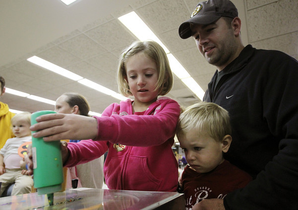 Danvers: Five-year-old Skylar Demsey, of Danvers, carefully squirts green paint onto her spin painting under the watchful eyes of her brother Finn, 2, and her father Mike, on Thursday evening at the Peabody Institute Library in Danvers. David Le/Salem News