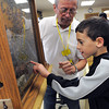 Topsfield:<br /> Thorpe Elementary School 2nd grader Andrew Makrakis points toward the queen honey bee at the honey bee hive exhibit at the Topsfield Fair. Ed Makarewicz is manning the exhibit.<br /> Photo by Ken Yuszkus, The Salem News,  Wednesday, October 09, 2013.