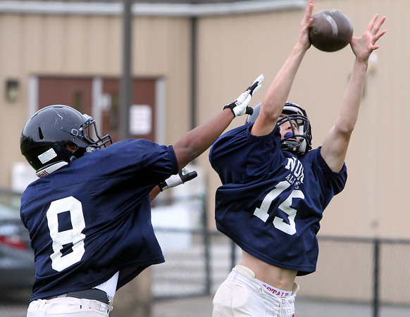 Middleton: North Shore Tech sophomore wide receiver Paul Lazzaro catches a ball over junior cornerback Ricky Valenzuela at practice. David Le/Salem News