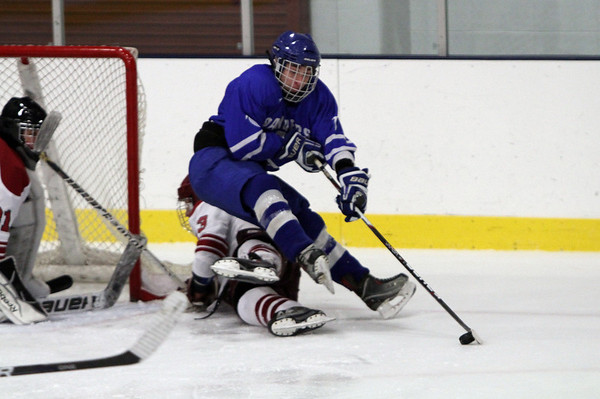 Danvers' Rob Buchanan gets upended by a Gloucester defender while controlling the puck. David Le/Staff Photo