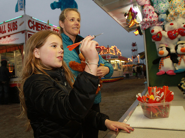 Tenley Williamson, 8, of Marblehead, prepares to throw a prize winning dart at the carnival on Devereaux Beach as her mother Jenny Williamson, looks on. David Le/Staff Photo