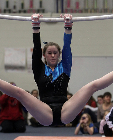 Danvers gymnast Emily McPherson winces as she completes a turn on the bars on Friday. David Le/Salem News