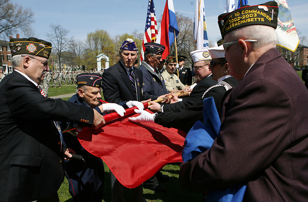 The Salem Veterans Council unfurls a replica 1636 Massachusetts Bay Colony Flag during the 375th Anniversary Celebration of the National Guard on the Salem Common on Saturday morning. David Le/Staff Photo