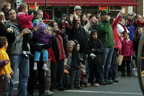 Large crowds of peope wave to Santa Claus along Cabot St during the annual Beverly Holiday Parade. David Le/Salem News