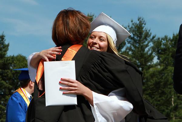 Danvers High School senior Catherine Vega hugs Principal Susan Ambrozavitch after receiving her diploma on Saturday afternoon. David Le/Staff Photo