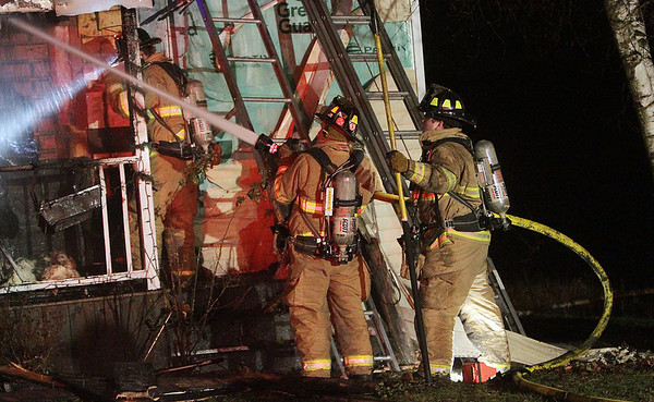 Hamilton: A couple local firefighters spray water through one of the front windows of a Beech St. home which caught fire Thursday evening. David Le/Salem News
