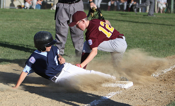 Peabody: In a cloud of dust Peabody National secondbaseman Aaron Dollin slides safely into third base as Danvers National thirdbaseman Nate Sweeney is too late applying the tag in the teams' game Wednesday evening at Cy Tenney Park in Peabody. Photo by David Le/Salem News