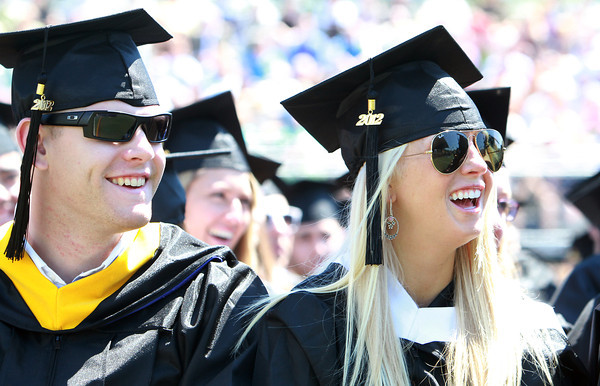 Endicott College seniors John Locke and Michelle Loizzo, laugh during a speech during Commencement on Saturday morning. David Le/Staff Photo