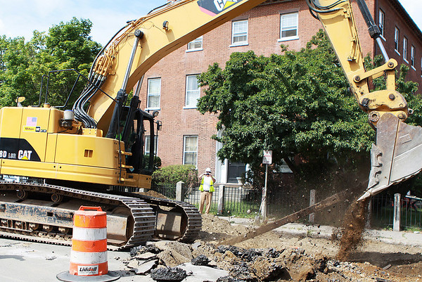 Salem: A construction worker on Bridge St. in Salem uses an excavator to snap an old hidden trolley rail that was found beneath the street. Construction will be inhabiting Bridge St. as workers make a push to remove all rails the length of the street so new gravel and dirt can be layered in order to create a stronger foundation for the street. Photo by David Le/Salem News