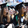 Endicott College seniors Courtney Linehan, left, and Karen Link, right, smile as they listen to Commencement Speaker Salome Thomas-EL, on Saturday morning. David Le/Staff Photo
