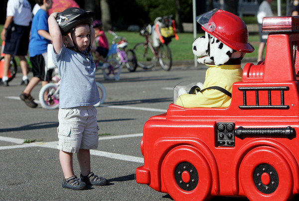 Nate Pasquarello, 2, of Beverly, is very perplexed when a talking fire dog approached him at the Bike Safety event at Beverly Homecoming at Lynch Park on Monday evening. David Le/Staff Photo
