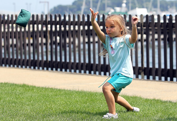 Annie Swanson, 4, of Salem, plays bean bag toss on the back lawn of the House of 7 Gables on Thursday afternoon. David Le/Staff Photo