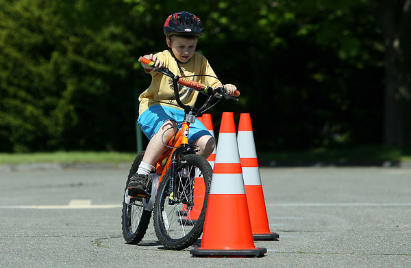 Anthony Poretsky, 6, of Peabody, carefully manuevers his bike through a cone obstacle in the Liberty Tree Mall parking lot during the Danvers Kiwanis Club Bike Rodeo on Saturday morning. The Kiwanis Club and Beverly Hospital joined forces to raise awareness for bicycle-related injuries. There was a skills course, bike and helmet fittings, safety testing stations and free bike helmets for participating. David Le/Staff Photo