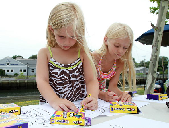 Sisters Caseigh, 4, and Sully McDonough, 7, of Leominster, color in dog pictures during a fundraiser for the Salem Play Areas for Canine Exercise at Leslie's Retreat Dog Park in Salem on Saturday morning. David Le/Staff Photo
