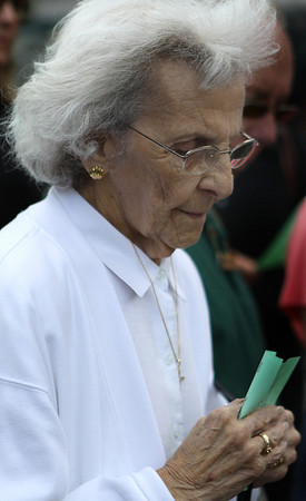 """Salem: May Pinault, the widow of Rollie Pinault, holds her hands together in prayer with her head bowed at the """"Four Trees"""" Dedication ceremony held on July 1st just outside the Museum Place mall in Salem. Members of The Essex condo raised money to plant 4 trees to commemorate the lives of loved ones and other residents in the building that have since passed. Photo by David Le/Salem News"""