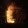 A couple Beverly firefighters try and contain a massive fire that started in an apartment complex on Folley Pond Road as they wait for assistance from other departments on Wednesday night. David Le/Salem News