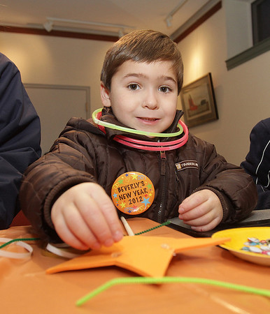 Beverly: Louie Spychalski, 5, of Danvers, smiles as he decorates a New Year's Eve star on Saturday night at the Beverly Public Library. David Le/Salem News