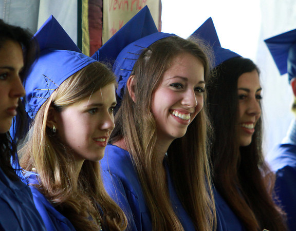 Waring School seniors from left, Emily Glaenzer, Rebecca Patey, and Ally Colarusso, smile at the opening remarks from headmaster Peter Smick during the Commencement Ceremony on Friday afternoon. David Le/Staff Photo