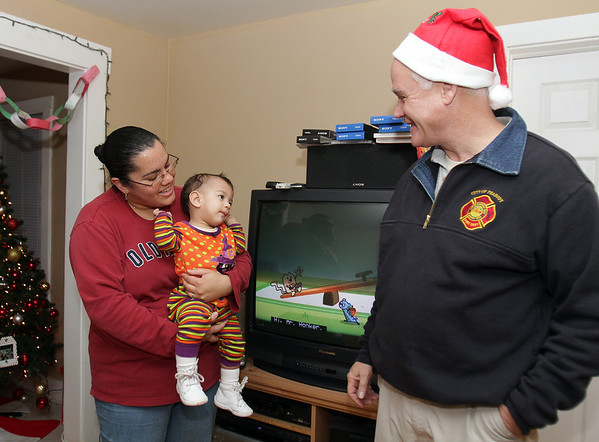 Peabody: Melanie Pena, of Peabody, holds her daughter McKenzie, 1, as they thank Peabody Veterans Agent Chris Tighe, for delivering the family some Christmas gifts on Wednesday afternoonb. David Le/Salem News