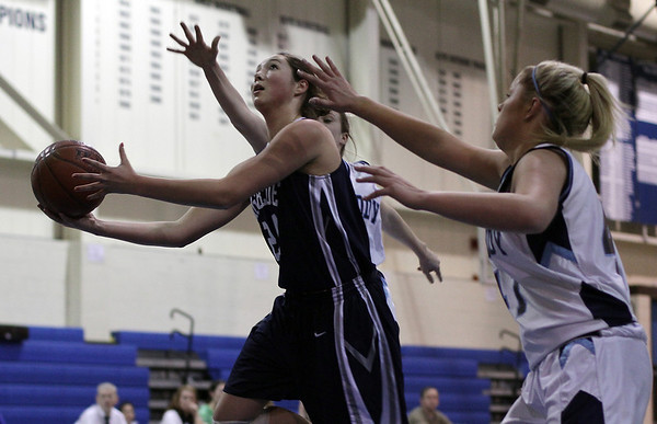 Swampscott's Ara Talkov (24) left, drives to the hoop while being defended by two Peabody players. David Le/Salem News