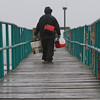 A fisherman walks down the pier at the Swampscott Yacht Club on a rainy Tuesday afternoon. David Le/Staff Photo