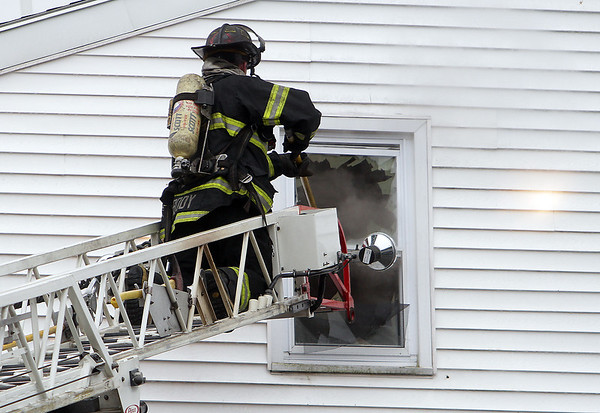 Peabody: A Peabody firefighter breaks through the glass on the third floor of a burning building on Friday afternoon. David Le/Salem News