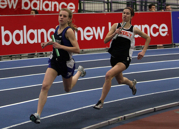 Peabody's Heather MacLean, left, and Beverly's Caitlin Harty, right, compete during the third leg of the 4x400 relay. David Le/Salem News