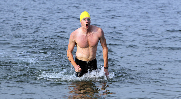 Brian Wettach, of Wakefield, is the first swimmer out of the water during the Ipswich YMCA Triathalon at Crane's Beach on Friday evening. David Le/Staff Photo