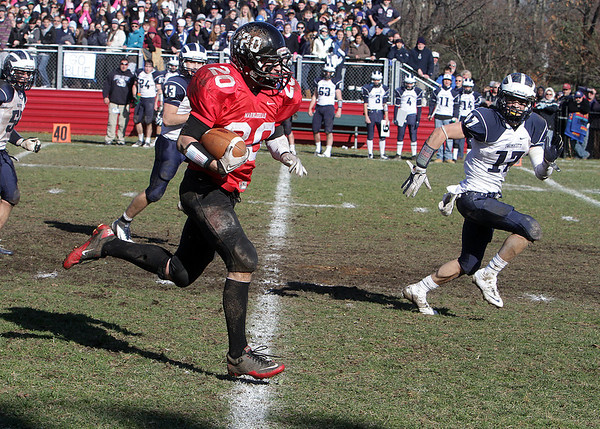 Marblehead running back Will Quigley (20) beats Swampscott defensive back Richard Sullivan (17) in a foot-race to the endzone for a long touchdown run. Quigley added another long TD run to lead the Magicians over the Big Blue 21-7 on Thanksgiving Day. David Le/Salem News