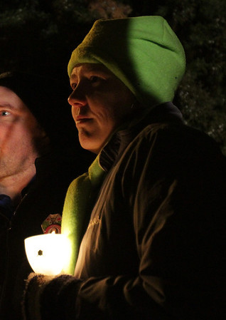 The face of Tracie Novack, aunt of former human service worker Stephanie Moulton, of Peabody, who was allegedly murdered by a patient last January, is illuminated by a candle at a vigil held on Wednesday. David Le/Salem News