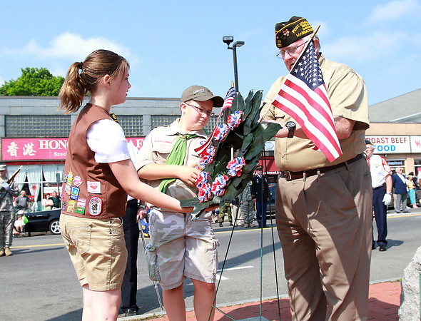 Danvers Girl Scout Braiden Devitt, left, and Boy Scout Mike Shannon, help Commander Dick Moody, of the Color Guard, place a ceremonial wreath in Danvers Square on Monday morning. David Le/Staff Photo