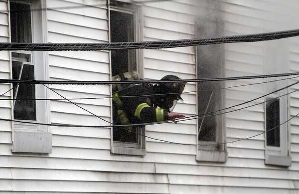 Peabody: A firefighter leans out of the second story window of a 3-alarm blaze as they try to combat the fire on Friday afternoon.  David Le/Salem News