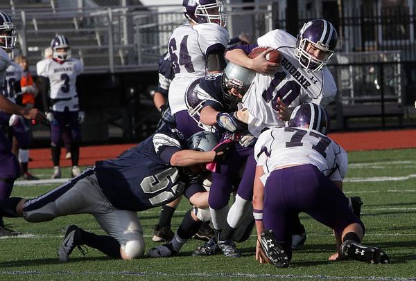 Hamilton-Wenham's Ryan Foringer (52) drags down Bourne quarterback Jason Moriarty. David Le/Salem News
